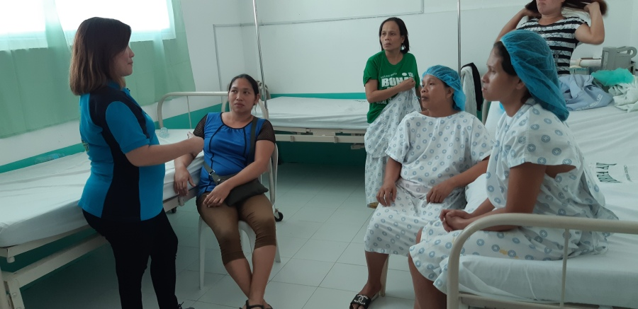 Women listen to a medical worker of Ziga Memorial Hospital prior to ligation